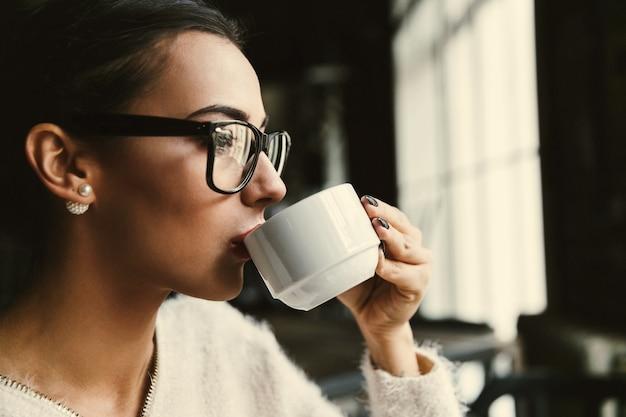 レディーはカフェでコーヒーを飲みながら彼女の時間を楽しんでいます