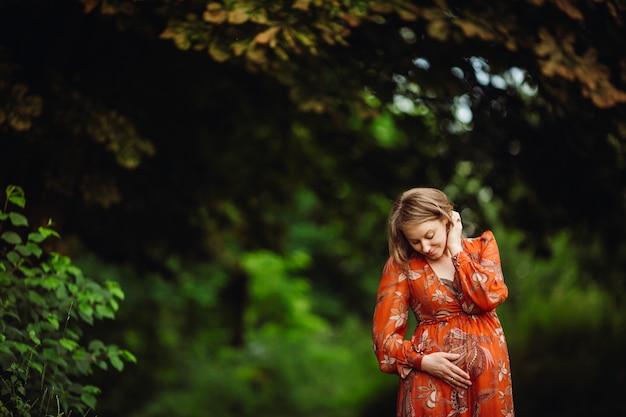 美しい妊娠中の女性、オレンジ色のドレスでポーズを取る