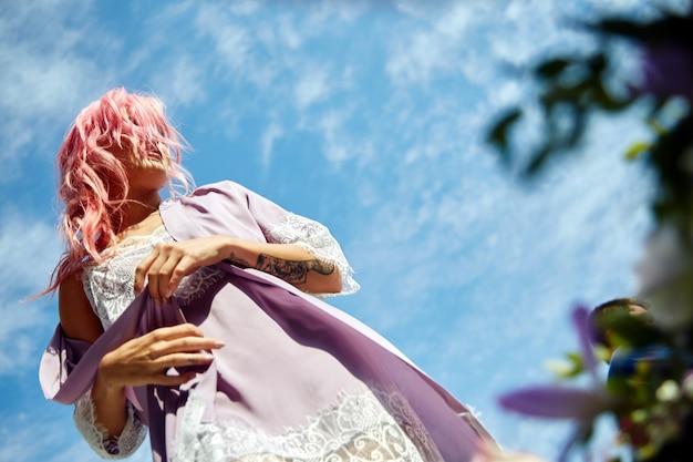 Женщина с розовыми волосами в фиолетовом халате и кедах стоит перед голубым небом