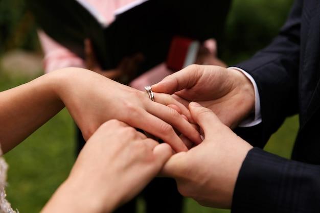 新郎は結婚指輪を花嫁の指に置きます