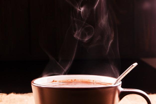 Аромат поднимается над чашкой кофе
