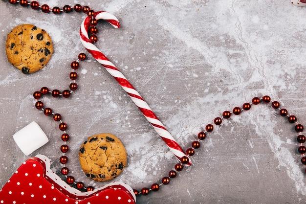 赤い白いキャンディー、クッキー、マシュマロは灰色の床に横たわっています