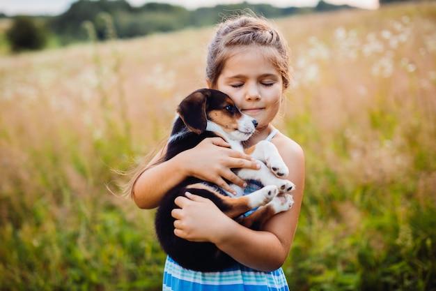 小さな女の子は彼女の腕に子犬を保持する