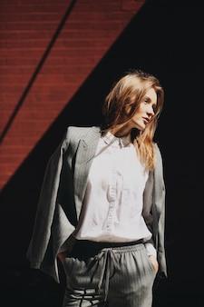 灰色のスーツで現代の若い女性は、灰色のレンガの壁の前にポーズ