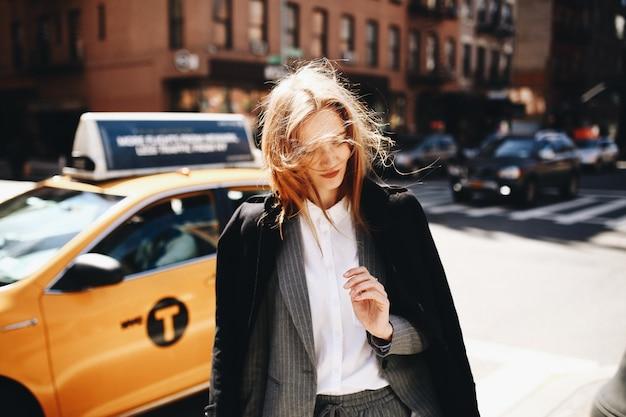 黒いコートのブロンドの女性は、ニューヨーク市のどこかの日当たりの良い通りに立っています