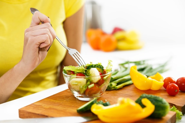 Крупный план женщина, есть салат на кухне