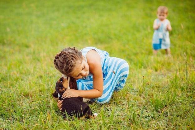 少女はフィールドに座って小さな子犬を抱擁
