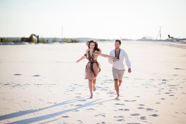 明るい刺繍の衣服を着た裸足のカップルが白い砂の上を走る