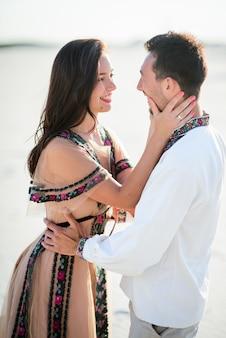 白い砂の上に明るい刺繍の服を抱きしめる柔らかい裸足のカップル