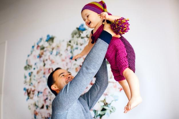 Отец поднимает маленькую девочку в розовом костюме