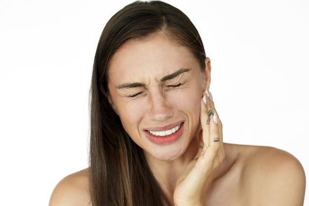 女性は歯痛を示す彼女の頬の上に指を保持する