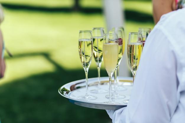 白い服を着たウェイターがシャンパンのフルートを入れたトレイを持っています
