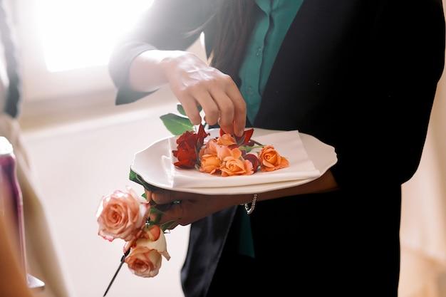 女は、繊細なオレンジのバラの芽を白いプレートに置く