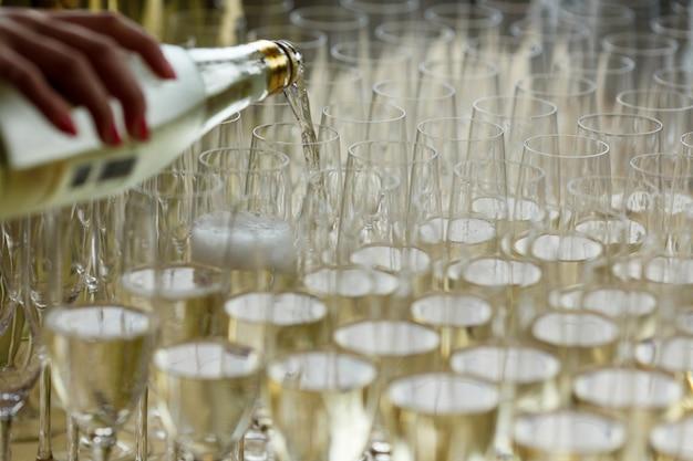 ウェイターがシャンパンを眼鏡に注ぐ