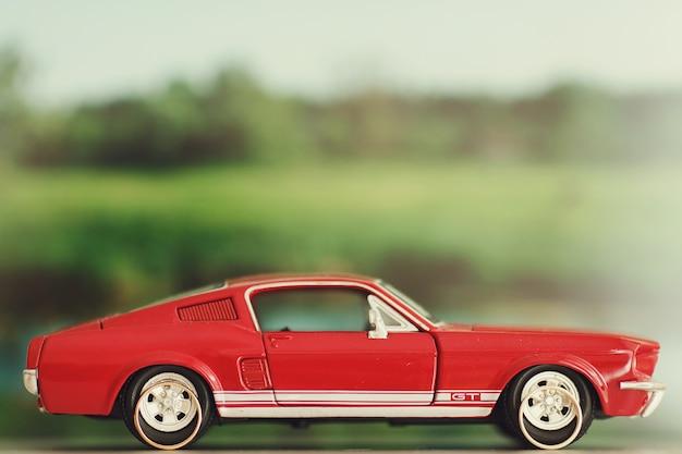 結婚指輪はおもちゃの赤いムスタングの車輪の後ろに横たわっている