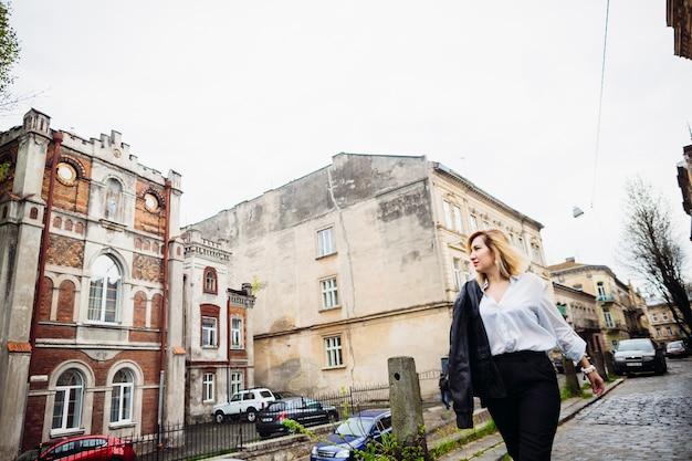 通りに沿って歩く美しい女性