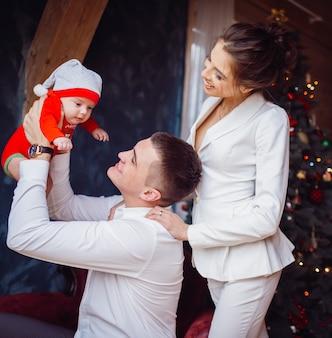 Отец держит на руках свою дочь и стоит рядом с матерью