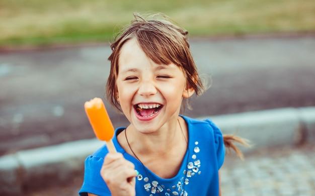 彼女の腕の中にオレンジ色のアイスクリームで笑っている少女