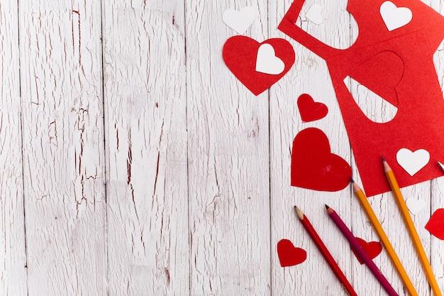 バレンタインデーのハガキの要素は、木製のテーブルに横たわっています