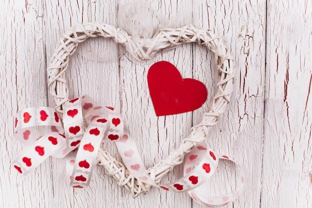 赤いリボンと装飾的な白い心は、白い木製のテーブルにある