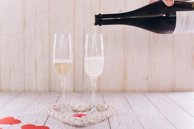 Человек наливает шампанское в бокалы на белом деревянном столе