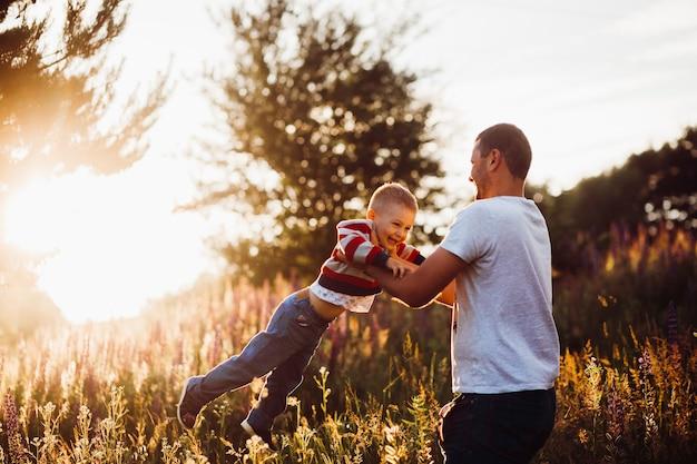 男は夜の太陽の光の中でフィールド上にポーズを上げる彼の息子を投げる