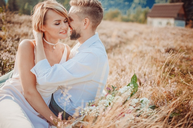 恋人を包み込み、芝生に座っている素敵なカップル