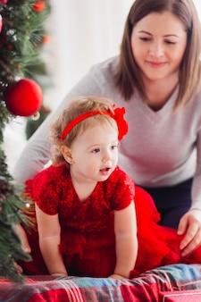 Очаровательная мать и маленькая дочь в красном платье