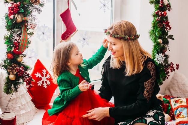 Мама играет с маленькой дочкой, перед ярким окном, украшенным на рождество