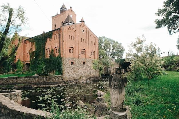 История красивый кирпичный и каменный замок, покрытый лианами