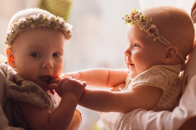 幸せなお母さんとお父さんは、明るい窓の前に腕におかしい双子と一緒にポーズを取る