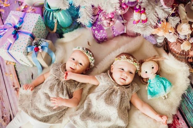 Девочки-близнецы лежат под розовой елкой