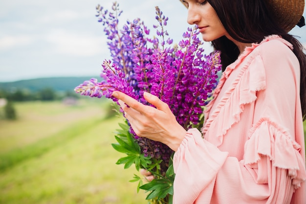 干し草の帽子の女は、フィールド上のラベンダーの花束とポーズ