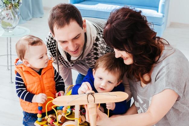 Мать, отец и сыновья, играющие с игрушками