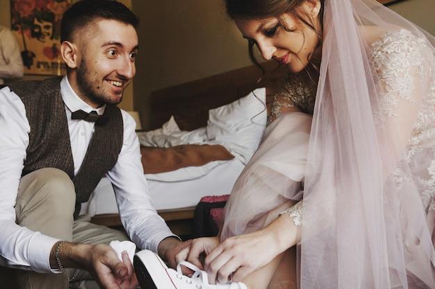 Жених помогает очаровательной невесте в розовом платье, чтобы надеть койки