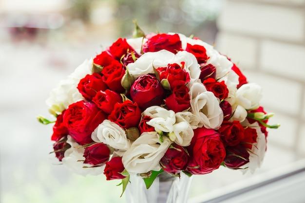 暗い赤と白のバラで作られた素晴らしいブーケはグラスの中に立つ