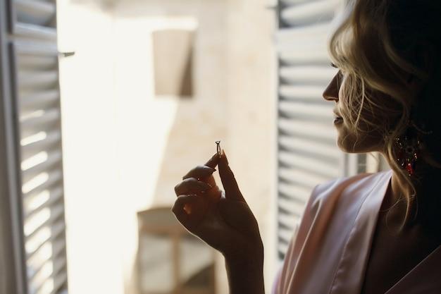 ピンクのシルクローブの女性は、彼女の指に結婚指輪を保持しています