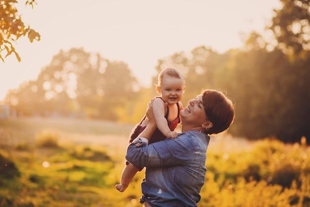 Женщина веселится с маленькой девочкой, стоящей в лучах золотого солнца