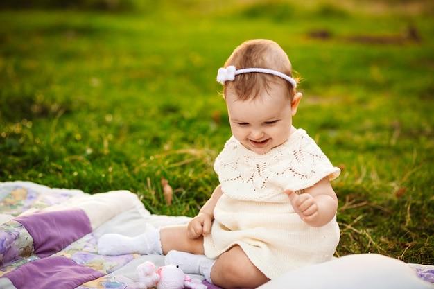 Пухленькая девочка сидит на белом одеяле