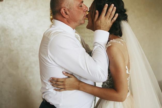 花嫁の父親が豪華なホテルの部屋に立って彼女の顔を柔らかくキス