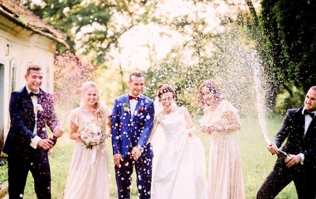 新婦や花嫁の前に立つ輝くシャンパンで、新婦たちがボトルを開きます