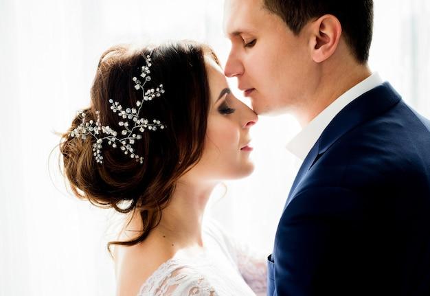 明るい窓の前に銀の花輪が立っている男女の優しいタッチ