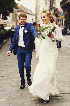 Веселая свадебная пара держит друг друга руками, бегущими по тротуару вдоль улицы