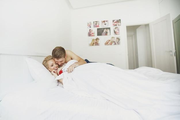 幸せな男は眠くて金髪の女性の後ろに抱擁し、彼女の赤い花をベッドの上に与える