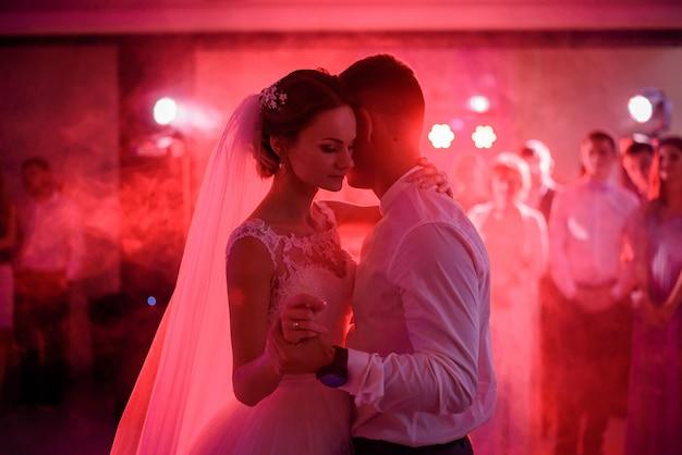 花嫁と新郎は赤いディスコライトでお互いを柔らかく踊る