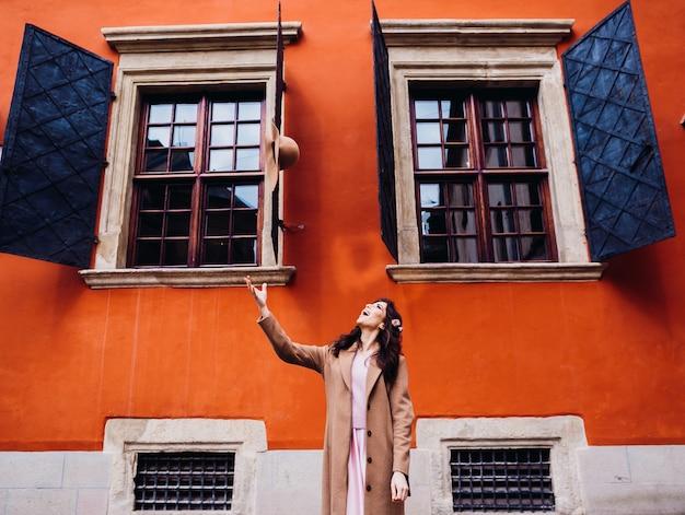 女はオレンジハウスの前に立ち、彼女の帽子を投げる