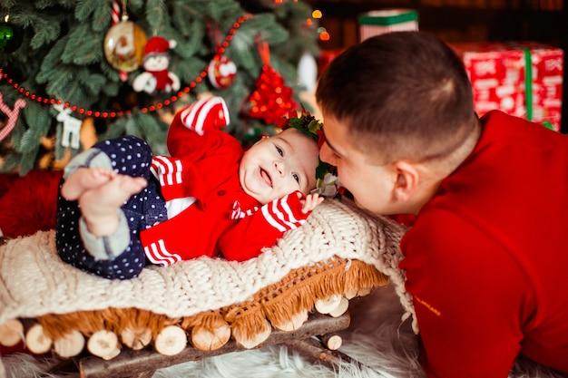 Папа наклоняется к своей маленькой дочери, пока она лжет перед рождественской елкой