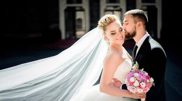 花婿のベールを風が吹き飛ばし、新郎は彼女のひよこにキスをする