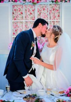 花嫁、新郎、お互いに優しい夕食のテーブルでキス