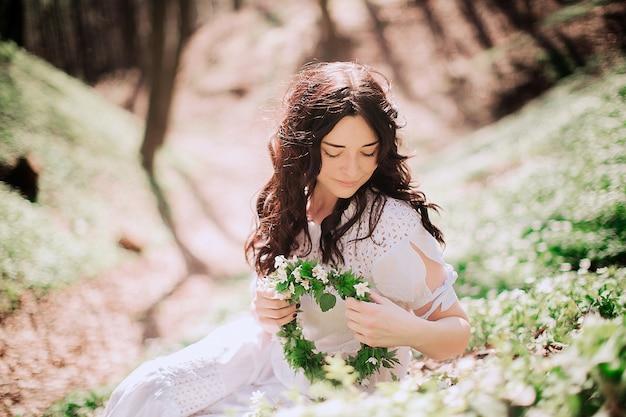 ブルネットの女性は緑の草に座って彼女の髪を修正